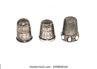 Three Silver Thimbles on White Background