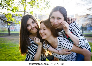 Three similar to each other sisters girls hugging. Group of friend enjoying their time out. Make a mustache out of the hair. Strong back light. Lens flare. Selective focus.