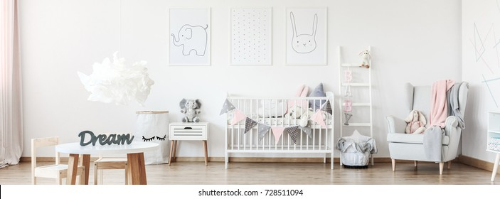 Three simple posters hanging on white wall in cozy room for baby