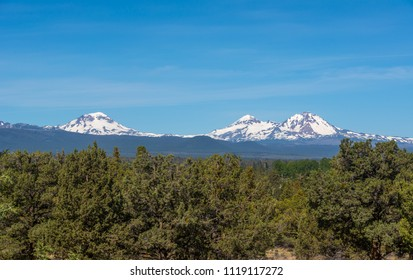 Three Sisters, Cascade Range volcanoes in Oregon, photographed from about 2 miles north of Tumalo, Oregon. The volcanoes are unusually close together and all about the same elevation, 10,000+ feet.