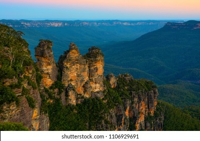 Three Sisters landmark in front of a backdrop of the Blue Mountains landscape just after sunset in NSW, Australia