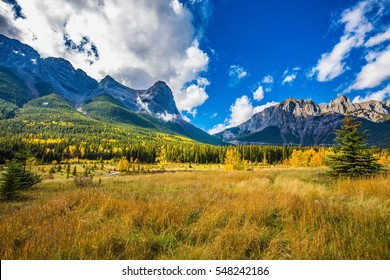 "The ""Three Sisters"" mountains in Canadian Rockies. Concept of trekking. Shining sunny day in Canmore. Mountain peaks are covered with white clouds"
