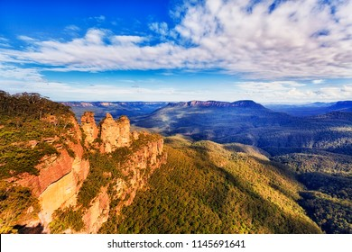 Three sisters rock cliffs natural landmark with Mt Solitude in a distance over massive valley seen from Echo point lookout at Katoomba town - Blue Mountains national park.