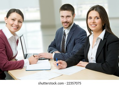 Three sitting businesspeople looking at camera