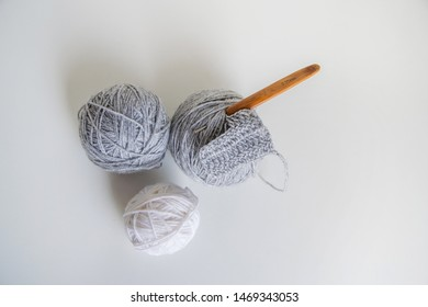 three skein of wool yarn for crochet, gray ball of yarn, a white ball of yarn, a crochet hook with a wooden handle on a white background