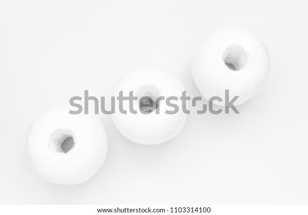 three skeins of white thread on white background, close-up abstract background