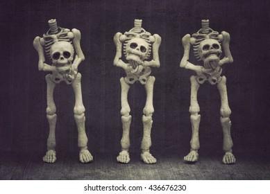 Three skeletons holding their own head with black background grungy textured
