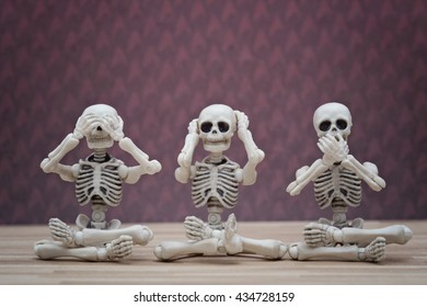 Three skeletons sitting pose hear no evil, see no evil, speak no evil
