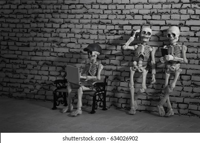 Three skeletons standing with a smartphone and laptop in their hand