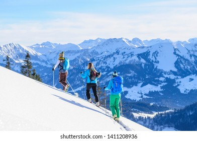 Three ski mountaineerers ascending to mountain top in austrian alps on a sunny afternoon