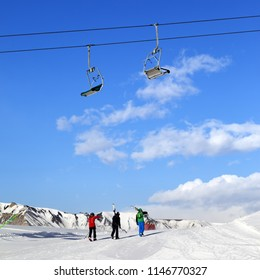 Three skiers on snowy slope at sun winter day. Caucasus Mountains in winter, Shahdagh, Azerbaijan. Square photo.