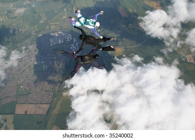 Three skydivers doing formations