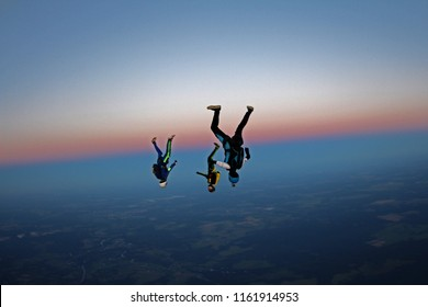 Three skydivers are falling in the evening sky.