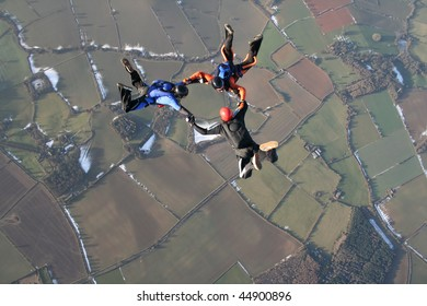 Three skydivers in free fall with snow in the background