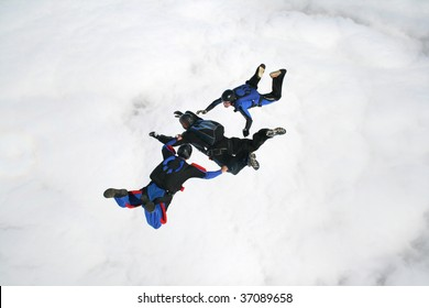 Three skydivers in freefall with a bank of clouds beneath them