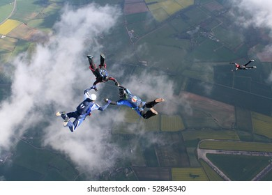 Three skydivers in freefall with a fourth one below them