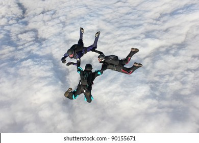 Three skydivers in freefall over bank of clouds