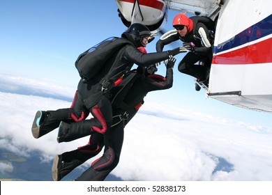 Three skydivers jump from a plane