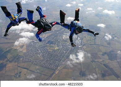 Three skydivers in a line behind each other with a town in the background