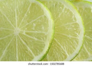 Three sliced green lemon top view fill frame