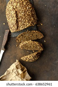 Three slices of bread with sunflower seeds, oat flakes and white sesame. On a dark background.
