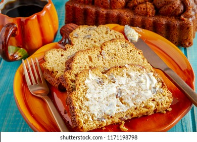 Three slices of fresh baked pumpkin bread with butter on pumpkin shaped plate with cup of coffee sitting on blue wooden table