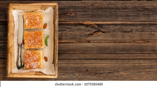 Three slices of homemade semolina cake on a wood vintage rustic table background with mint tea. Overhead or top view composition
