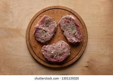 Three slices of raw meat spiced with rosemary, placed on round wooden cutting board, viewed from above on wooden background