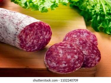 three slices of salami, pork meat, on wooden table, with green leaves