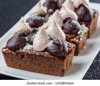Three Slices of Triple Chocolate Torte with icing sugar on a white serving dish and dark background