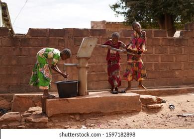 Tres Pequeñas Niñas Africanas Gestionan Alegremente Una Bomba De Agua Para Recolectar Agua