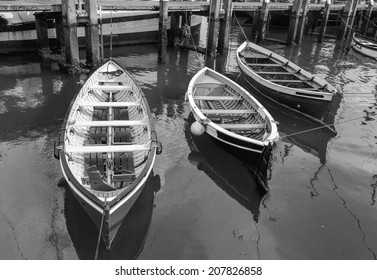 Three small boats in marina in Terschelling, Netherlands (black and white)
