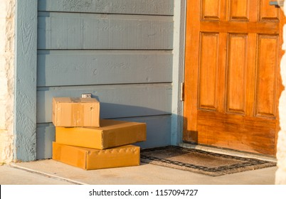 three small boxes left on the front door. first thing in the morning sunrise on early package delivery. Early bird gets the worm.