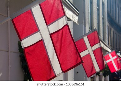 Three small bright red Danish flags lit by the sun, hanging in sequence from a building in Copenhagen, Denmark
