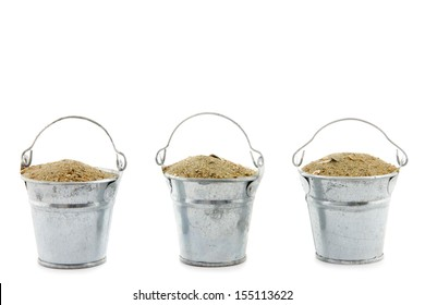 three small buckets filled with sand isolated on white