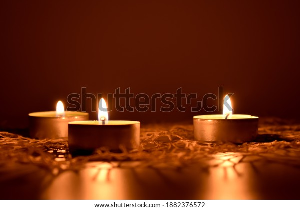 Three small burning candles and a bright napkin.