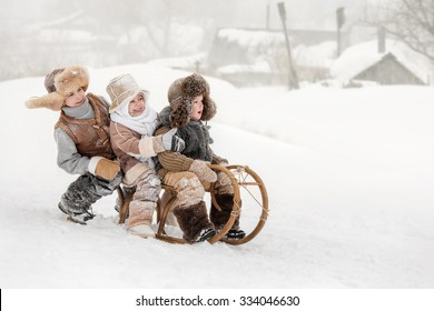 Three small children slide down hills on sleds in winter sunny day