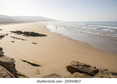 Three small figures of people in an idyllic sand beach near Agadir in Morocco.
