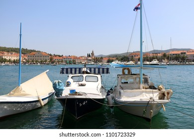 Three small fishing boats in harbor of Vela Luka, Korcula island, Croatia. Vela Luka is a popular summer travel destination.
