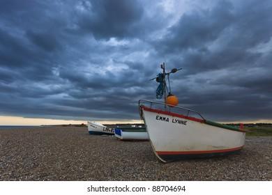Three small fishing boats on the shingle beach of Cley Next The Sea on the North Norfolk coast