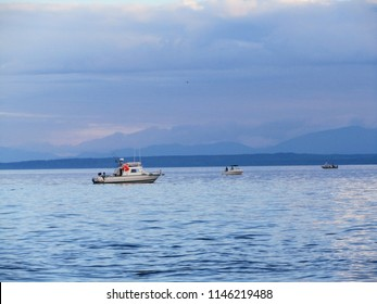three small fishing boats trolling for salmon on the coast of Vancouver Island, British Columbia