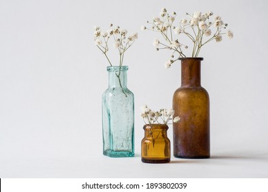 Three small glass handmade vases with white dried wild flowers. Brown and blue glass vintage bottles. Antique interior decoration objects.  - Shutterstock ID 1893802039