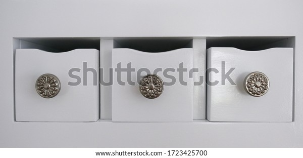 Three small kitchen drawers with brushed nickel knobs in kitchen.
