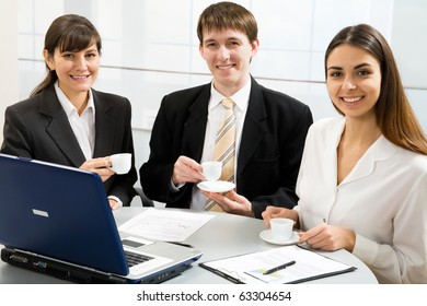 Three smiling attractive young business people on coffe break