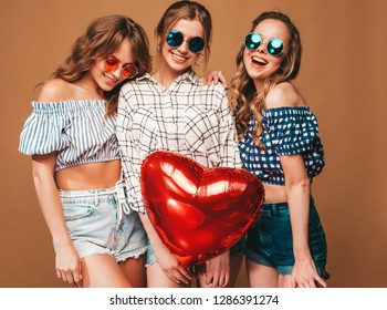 Three smiling beautiful women in checkered shirt summer clothes.Girls posing on golden background.Models with heart shape air balloon in sunglasses.Ready for celebration Valentine's Day,Symbol of love