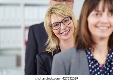 Three smiling business people stand in a line while wearing suit jackets near shelf with binders