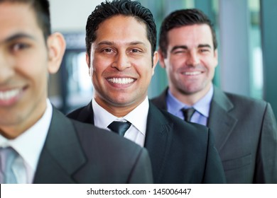 three smiling businessmen standing in a row