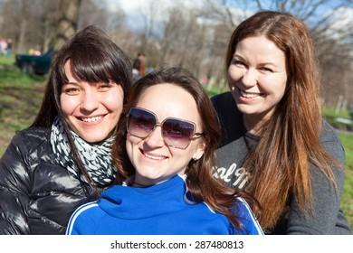 Three smiling Caucasian attractive women looking at camera