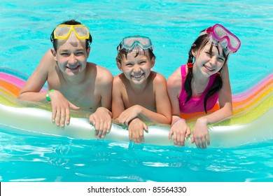 Three Smiling Children in Pool