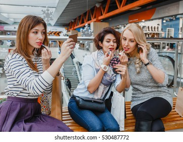 Three smiling friends putting makeup while shopping in th mall